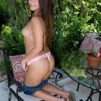 Eighteen year old black-haired Natalie Monroe strips to thong underwear on the patio in solo activity