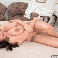 Tattooed brown-haired solo girl Cat Bangles reveals her massive titties during upskirt play