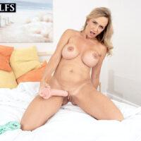 Big-boobed elder blonde Kenzi Foxx tweaks her nipples before masturbating with a dildo