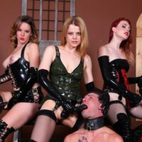 Dominant girls abuse masculine submissives with strapon penises while in latex apparel and boots