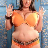 Giant boobed black-haired plumper Arianna Sinn slurps a nip during solo activity