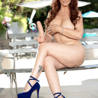 Huge-chested aged redhead Syren De Mer gets naked on a poolside patio in high-heeled shoes