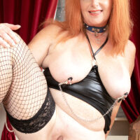 Buxom senior woman with red hair Melanie Taylor sports nipple clamps while paddling her huge ass