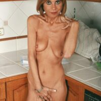 experienced housewife removes jeans and underwear to model nude in her kitchen