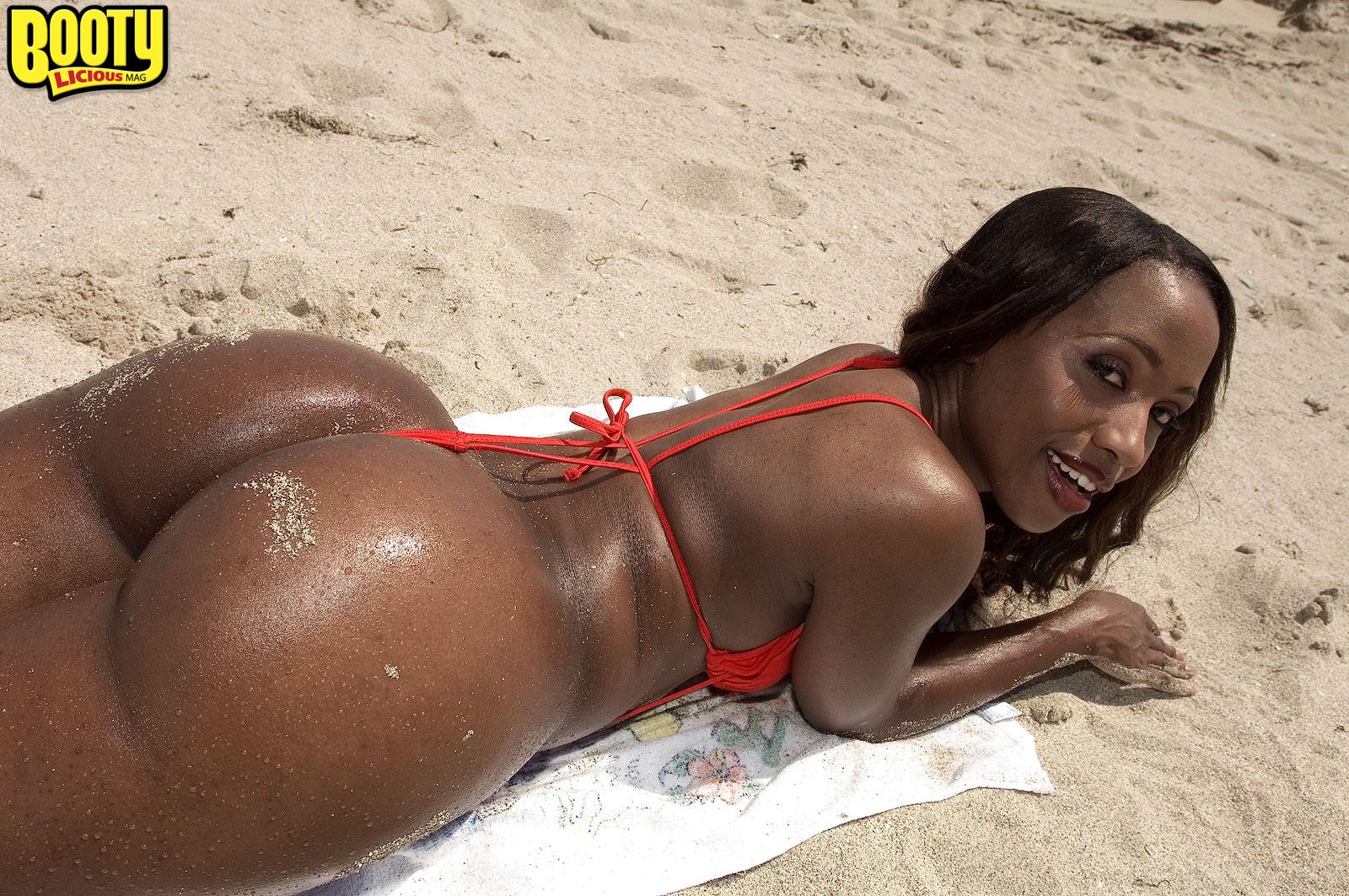 Ebony solo chick Sapphira demonstrating her massive booty on beach while wearing a red bathing suit