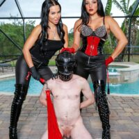 Black-haired Domme Kylie Rogue and another Mistress abuse a masked male sub beside a pool