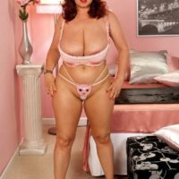 Chunky redhead Cherry Brady struts in her bra and panty ensemble plus a pair of pink pumps