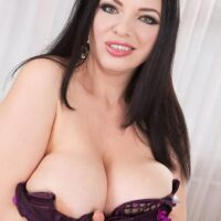 Dark haired MILF Joana Bliss extracts her big titties from lingerie in black fishnet hosiery