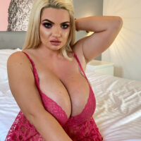Light-haired fatty sets her humungous breasts loose of lingerie on a bed in high-heeled shoes