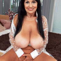 Large breasted brown-haired grandmother Mona Marley whips out her tanned lined assets before masturbating