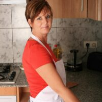 Mature housewife with short crimson hair looses her enormous naturals for her first naked poses