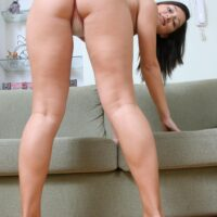 Brunette amateur with a seductive rump and diminutive boobies whips out her all natural beaver on a chesterfield