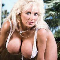 Elder pornstar Platinum Peaks releases her immense titties from hooter-slings in lace panties and heels