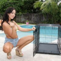 Dark haired mistress Adriana Lily pegs her sissy over a cage out on a poolside patio