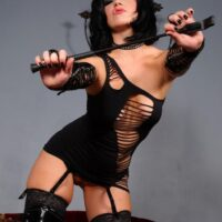 Beguiling brown-haired female Belle Noir spanks her sexy butt with a cane in a revealing ebony dress
