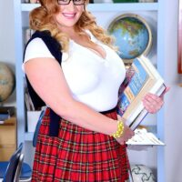 Big sandy-haired solo female Mya Blair posing in a coed uniform plus glasses and pigtails