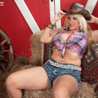 Curvaceous sandy-haired farm girl Rockell reveals her giant naturals and huge ass in a cowgirl hat