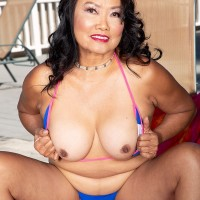 60 Plus Chinese MILF Mandy Thai peels off a rope bathing suit to get naked by a pool