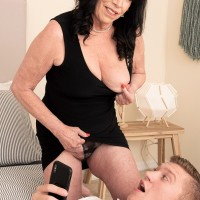 60 plus MILF Christina Starr seduces a young boy while going disrobed to the waist in a black dress
