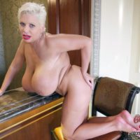 Aged platinum blond Claudia Marie wets her gigantic boobies while taking a shower