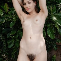 Amateur solo female Kasey Warner slipping shorts and bloomers over furry slit outdoors