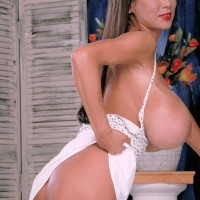 Oriental solo model Minka unveils her thicket with her gigantic titties on flash on a bed
