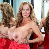 Japanese solo model Minka uncovers her immense boobs from a red dress afore a mirror