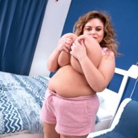 BBW Anna Katz tugs on her hard nipples after loosing her enormous boobies in a bedroom