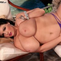 Enormous titted dark-haired Arianna Sinn plays with her hard nips after getting naked on a patio