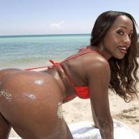 Ebony solo female Sapphira demonstrating enormous booty on beach attired crimson bikini
