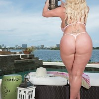 Golden-haired BIG SEXY LADY Holly Wood struts about in a thong swimsuit next to the ocean