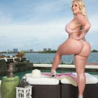 Light-haired BBW Holly Knob struts about in a thong bathing suit next to the ocean