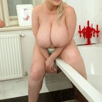 Light-haired BIG SEXY WOMAN Samantha Sanders looses her enormous knockers as she readies for a tub