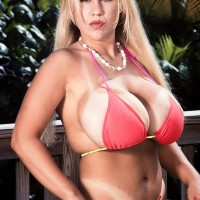 Platinum-blonde female Honey Moons demonstrates her tan lined melons on the patio in high-heeled shoes