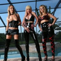 Platinum-blonde dominas Alexia, Tyler and Alina model latex wear in front of a swimming pool