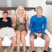 Ash-blonde grandma Cammille Austin masturbates a pair of cocks after seducing studs in a dress