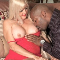 Blonde granny Marina Johnson salutes her ebony lover in red sundress and matching stilettos
