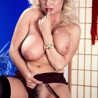 Ash-blonde MILF Michelle Willings holds her gigantic all natural tits in garters and nylons