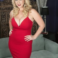 Blond MILF Rockell pinches her hard nips after unveiling her huge tits from a red dress