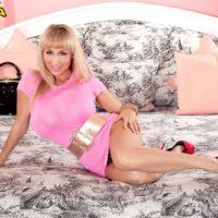 Platinum-blonde MILF Venera extracting gigantic tits adorned in heels on bed