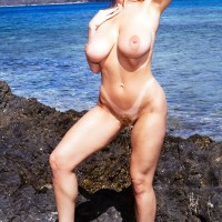 Yellow-haired solo female Danni Ashe rocks her superb boobs while nude as the surf comes in