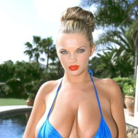 Light-haired solo female Ines Cudna sets her monster-sized natural titties loose from bathing suit top by the pool