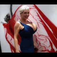 Blonde solo model Claudia Marie gargles on a nip after unsheathing her huge breasts