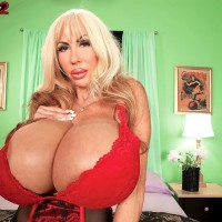 Blonde solo model Elizabeth Starr displays her monster hooters in a red brassiere