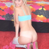 Platinum-blonde teenager Naomi Woods takes off her miniskirt and pulls down her white hosiery