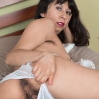 Brown-haired amateur Vivi Marie spreads her full bush on a bed in frilly white socks