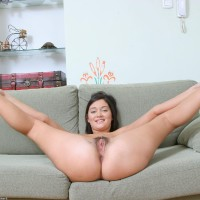 Brunette amateur with a wonderful rump and puny titties bares her all natural cunt on a couch