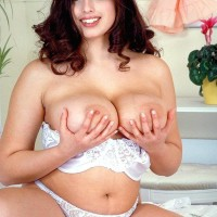 Brown-haired solo girl Kerry Marie letting giant all-natural fun bags fall free from melon-holder