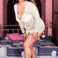 Dark-haired girl Lisa Miller sets her hefty knockers loose on her bed in milky undies