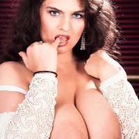 Dark-haired girl Lisa Miller sets her hefty knockers loose on her bed in milky undies